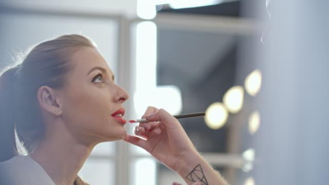 Transgender make-up artist applying red lipstick on female model