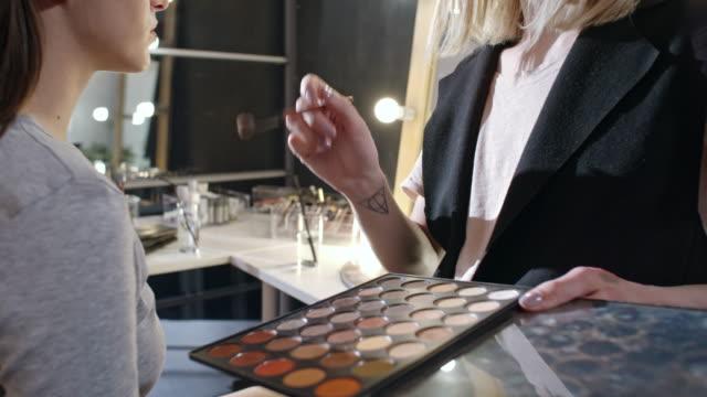 Transgender make-up artist preparing beautiful model for photo shoot