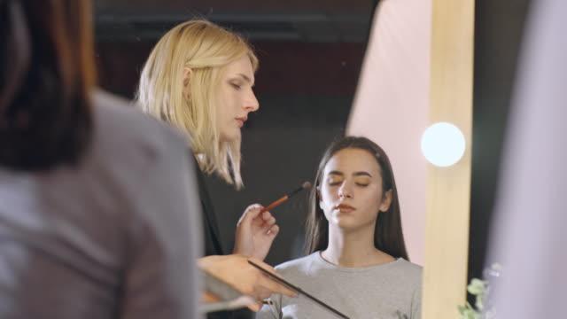 Transgender make-up artist working with grateful female model