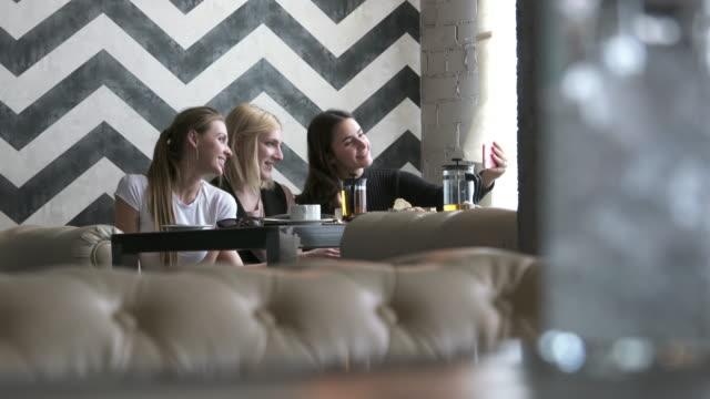 Transgender person and female friends taking selfie in restaurant