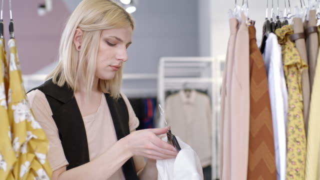 Transgender person choosing blouse in fashion boutique