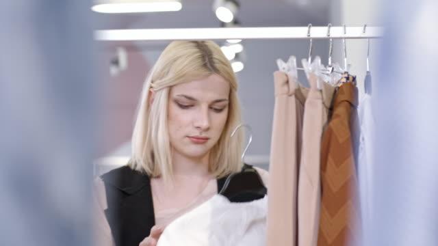 Transgender person choosing chiffon blouse