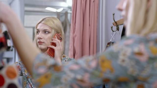 Transgender person talking on mobile phone in changing room