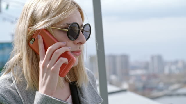 Transgender person talking on mobile phone on rooftop