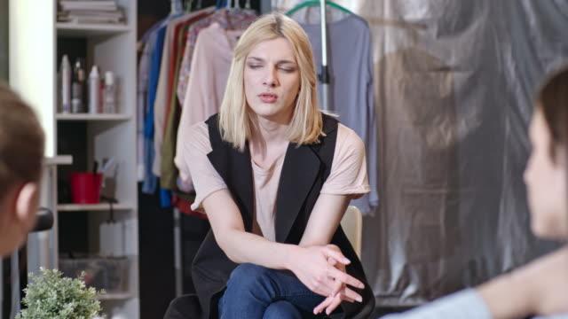 Transgender stylist talking to female friends in studio