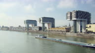 WS Transport ship moving in front of three Cranehouses and buildings in city / Cologne, North Rhine-Westphalia, Germany