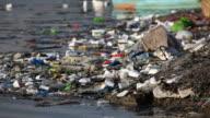HD trash along polluted river bank