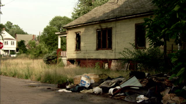 Trash and rubble sit in front of a burnt out home. Available in HD.