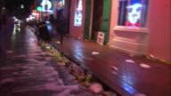 Trash litters a gutter and fills a trash bin after Mardi Gras.