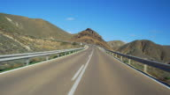 POV travel shot, empty serpentine highway and volcanic rock formations