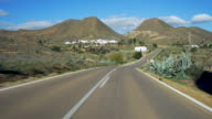 POV travel shot, lonely highway with white houses in desert hills