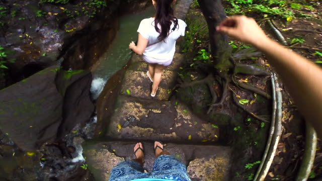 Traveler couple walking in a narrow crack with river during travel vacations in the Bali island recorded from personal perspective using action cam.