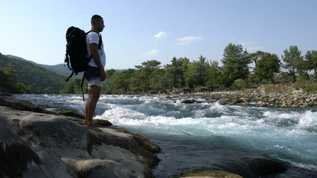 Traveler with backpack looks on a waterfall