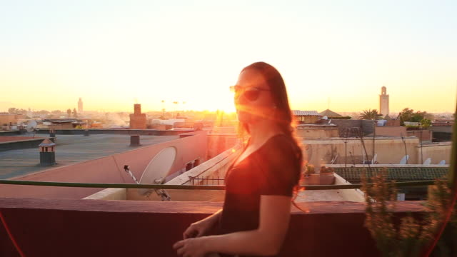 Traveler woman contemplating the stunning sunset over the Marrakech medina city from viewpoint terrace during travel vacations in Morocco.