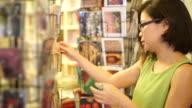 Ein Reisender Frauen Blick auf Postkarten außerhalb einer Buchhandlung und Souvenir-Shop.