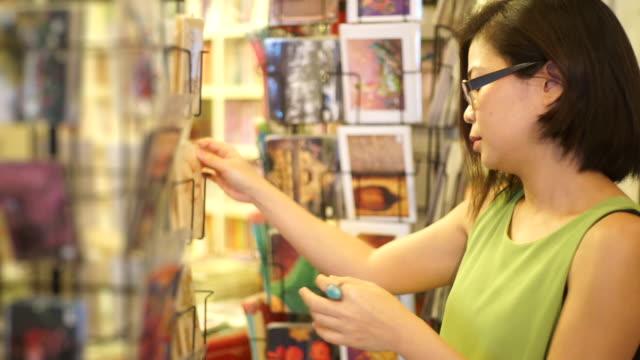 A traveler women looking at postcards outside a bookshop and souvenir shop.