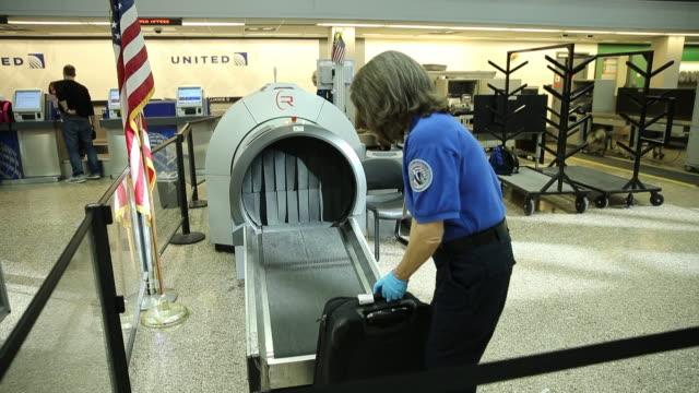 Travelers enter a security check in line inside a terminal at the Salt Lake City International Airport in Salt Lake City Utah TSA employees scan...
