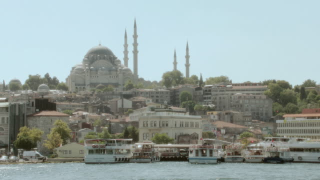POV Traveling along the Bosphorus Strait past docked boats and coastal properties with the Hagia Sophia in the distance / Istanbul, Turkey