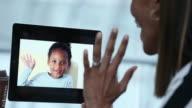 traveling mother talking to daughter on digital tablet