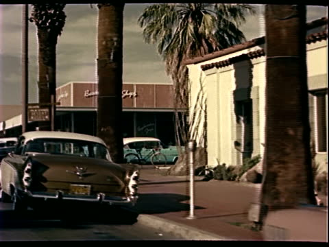 Traveling shot of downtown Palm Springs California late 1950s American cars parallel parked on street pedestrians stores including Palm Springs...