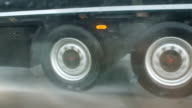Traveling thought dangerous thunderstorm on the highway, wheels of truck