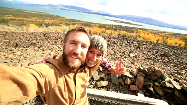 Traveling young couple taking selfie on mountain