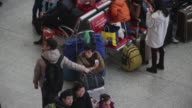 Travellers queue at the ticket check barriers in the main hall of the Shanghai Hongqiao Railway Station in Shanghai China on Friday Feb 5 People...