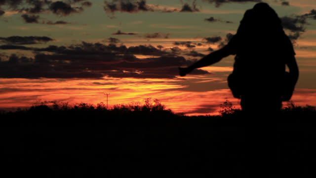 Travelling Man hitch-hiking in front of Sunset