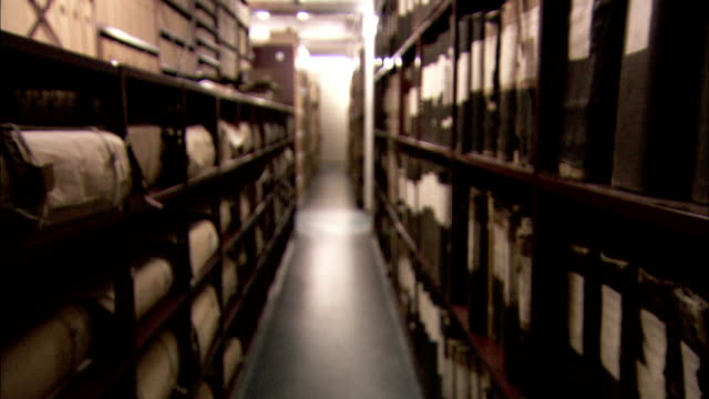 Travelling slowly along the stacks of a large storage room. Available in HD.