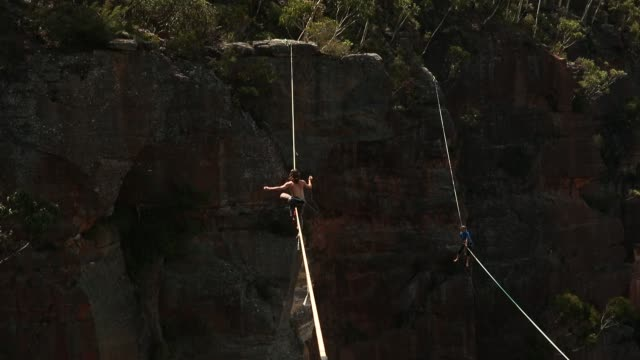 Travis Foster of the United States and Joseph Huard of Canada walk on highlines rigged between cliffs at Corroboree Walls in Mount Victoria on March...