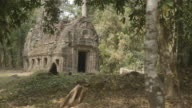 Trees surround an old stone building in the Angkor Wat temple complex in Cambodia.