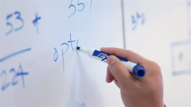 Trendy young businessman's hand writes on conference-room white-board