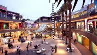 WS T/L Tri level open courtyard of Santa Monica Place luxury shopping mall at dusk with escalators connecting three floors of shops and restaurants / Santa Monica, California, USA