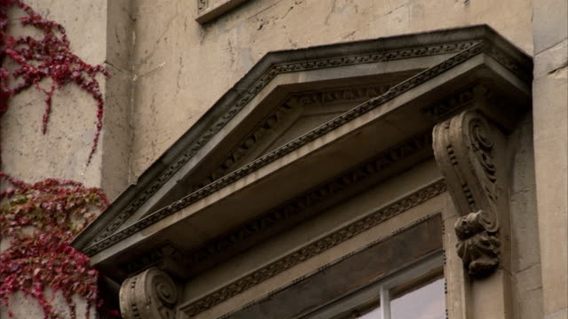 A triangular pediment tops a window on a townhouse. Available in HD.