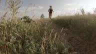 Triathlete trail runner follows trail through field at sunrise
