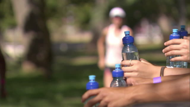 SLO MO CU Triathletes taking water bottles from supporters while running race in De Waal Park / Cape Town, South Africa