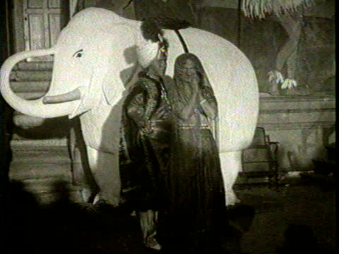 Tribal performers dancing and raising spears on a crowed dance floor / Performers in Middle Eastern costumes standing in front of a elephant prop on...