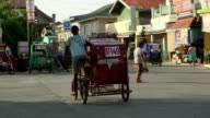 A tricycle taxi driver scans the street for a passenger
