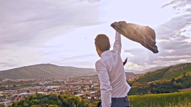 SLO MO Triumphant businessman on the hill