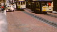 Trolleys riding on track / Pedestrians boarding trolley / POV of riding the car on hills / San Francisco Trolleys on June 01 1960 in San Francisco...
