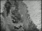 troops firing at downed soldiers / troops running through a trench