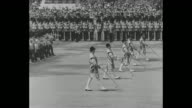 AERIAL troops in formation at the Horse Guards Parade Ground's Trooping the Colour / George V in bearskin hat on horseback / band slowly marches in...