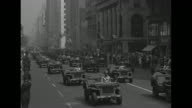 VS troops march on Fifth Avenue in Manhattan during rally to kick off Third War Loan drive for World War II war bonds / women watch from upper story...