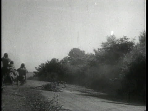 Troops on ground / Tank firing cannon / Cannon exploding / Wrecked German tanks / Tank driving down road