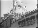 Troops wave from rail of USS West Point as it docks in NYC / troops march along dock and walk plank with supplies / troops wave to camera / aerial...