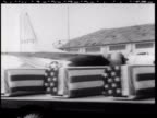 Truck carrying coffins covered in American flags at airport / soldiers and sailors standing at ease by military airplane / soldiers carrying American...