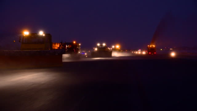 Truck deicing a road, by night