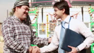 Truck driver shaking hands with a salesman, Ballabgarh, Haryana, India