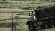 Truck driving across field down hill.