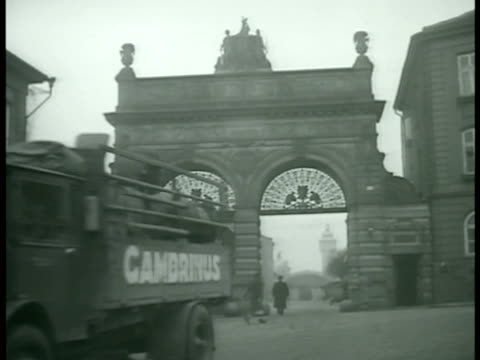 PLZEN CZECHOSLOVAKIA Truck driving out through arched gates of Pilsner Urqueli Brewery WS Men working on large beer barrel CU Glass of draft pilsner...